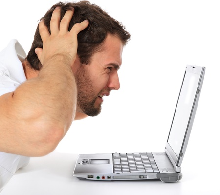 computer problems: Frustrato uomo seduto davanti al suo computer portatile. Tutto su sfondo bianco.