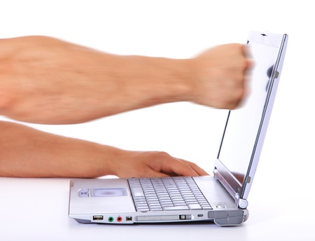 A person punches his laptop. All on white background.  photo