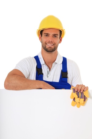 Construction worker standing behind white wall. All on white background. Stock Photo - 9780924