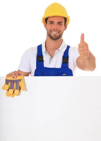 Construction worker making thumbs up while standing behind white wall. All on white background.  photo