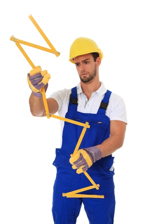 Clumsy construction worker holding folding ruler. All on white background.  photo