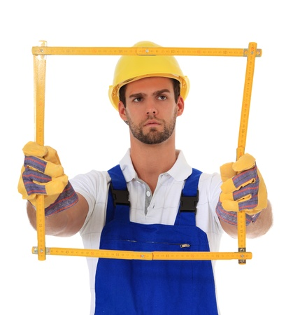 Construction worker holding folding rule. All on white background.  photo