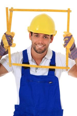 clumsy: Trabajador de construcci�n torpe mirando a trav�s de plegado la regla. Todo sobre fondo blanco.