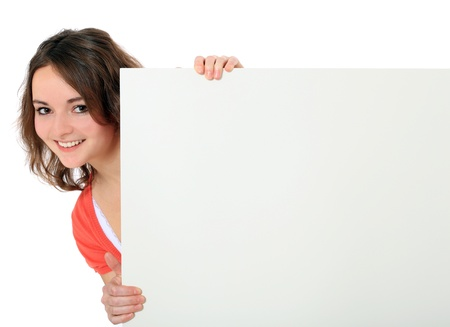Attractive young woman standing behind white board. All on white background.  免版税图像