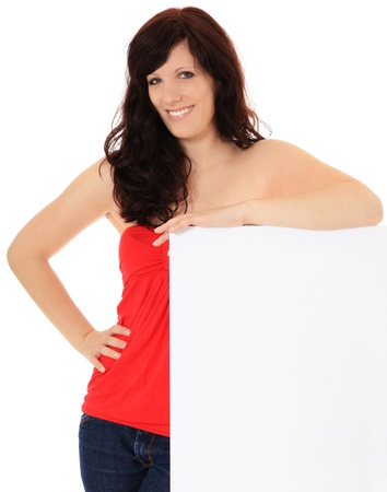 Attractive young woman standing next to blank white sign. All on white background. Stock Photo - 10057356