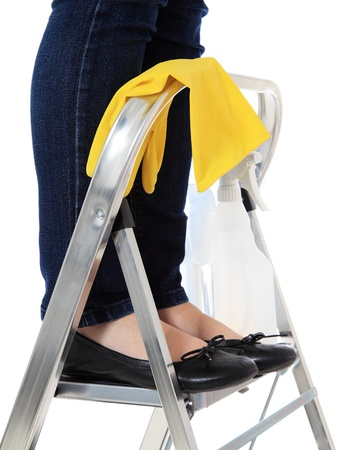 Woman standing on stepladder during housecleaning. All on white background.  photo