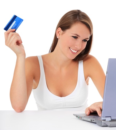 Attractive young woman using her credit card to buy things on the internet. All on white background.  photo