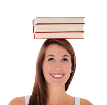 Attractive young woman balancing books on her head. All on white background.  photo