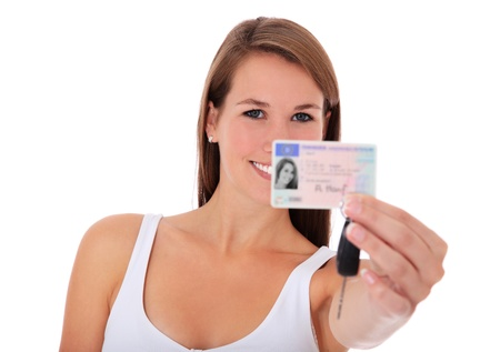 Attractive young woman showing her european driver license. All on white background.