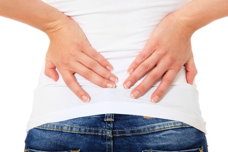 Attractive young woman suffers from back pain. All on white background.