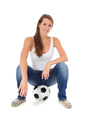 Attractive young woman sitting on soccer ball. All on white background.  Stock Photo - 10118499