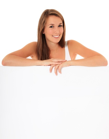 grown ups: Attractive young woman standing behind blank white sign. All on white background.  Stock Photo