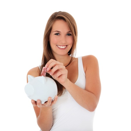 Attractive young woman puts money in her piggy bank. All on white background.  photo
