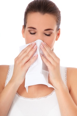 Attractive young woman suffers from hayfever. All on white background.