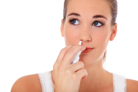 nosa: Atrakcyjna mÅ'oda kobieta przy użyciu spray do nosa. Wszystkie na biaÅ'ym tle. Zdjęcie Seryjne