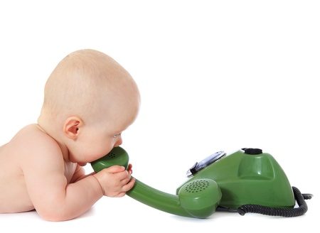toy phone: Newborn child playing with a green telephone. All isolated on white background. Stock Photo