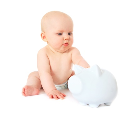 Newborn child playing with piggy bank. All isolated on white background.