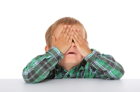 boyhood: Cute caucasian boy hides himself. All on white background.  Stock Photo