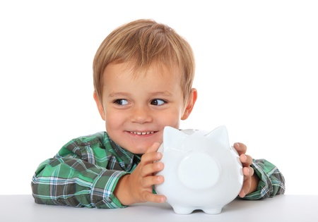 Cute caucasian boy with his piggy bank. All on white background.