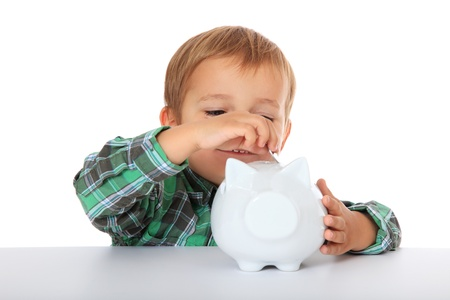 Cute caucasian boy puts money in his piggy bank. All on white background.