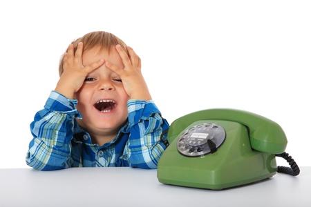 chłopięctwo: SÅ'odkie kaukaski chÅ'opak Å›mieje siÄ™ obok telefonu. Wszystko na biaÅ'ym tle.