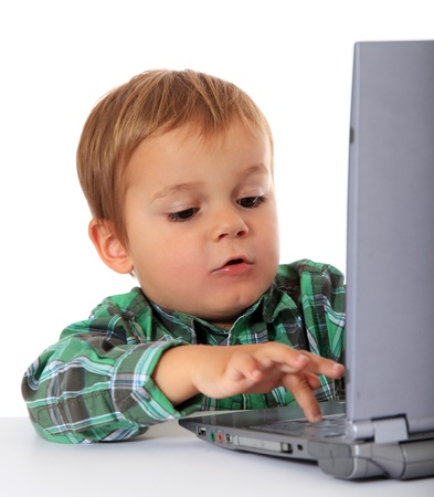 Cute caucasian boy using laptop. All on white background.  photo