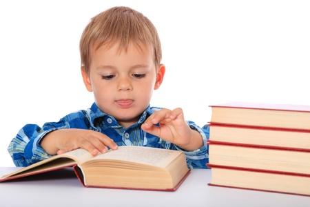 chłopięctwo: Cute Kaukaski chłopiec patrząc poprzez książki. Wszystko na białym tle.