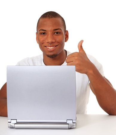 Attractive black guy showing thumbs up while using laptop. All on white background. Stock Photo - 10873528