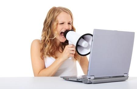 Aantrekkelijke jonge vrouw gebruikt megafoon tijdens de vergadering in de voorkant van een computer  laptop. Geïsoleerd op een witte achtergrond.