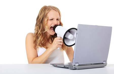 Attractive young woman uses megaphone while sitting in front of a computer / laptop. Isolated on white background.
