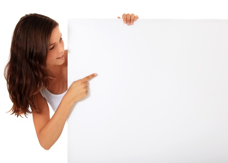 visualise: Attractive young woman pointing at blank white sign. All on white background.  Stock Photo