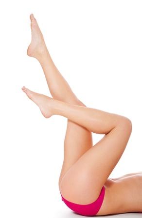 belles jambes: Jambes d'une femme séduisante en bikini. Isolé sur fond blanc.
