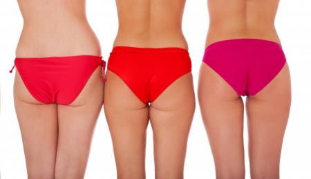 Achterkant van drie aantrekkelijke vrouwen in bikini. Geà ¯ soleerd op een witte achtergrond.