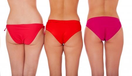 personas banandose: Parte trasera de tres atractivas mujeres en bikini. Aisladas sobre fondo blanco. Foto de archivo