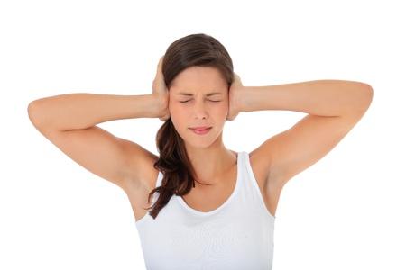 ruido: Mujer joven y atractiva mantener los oídos cerrados. Todo sobre fondo blanco.