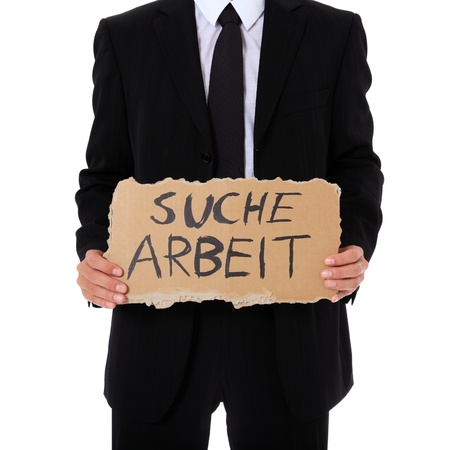 Businessman holding cardboard sign with the german term suche arbeit (Engl.: hunting for a job). All on white background.  photo