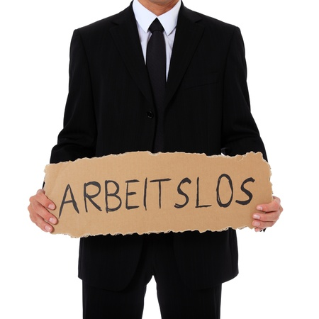 redundant: Torso of a businessman holding cardboard sign with the german term arbeitslos (Engl.: jobless). All on white background.