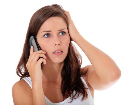 worries: Attractive woman gets shocking news during phone call. All on white background.  Stock Photo