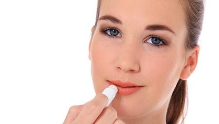 Aantrekkelijke jonge vrouw met behulp van lippenbalsem. Alle op een witte achtergrond.