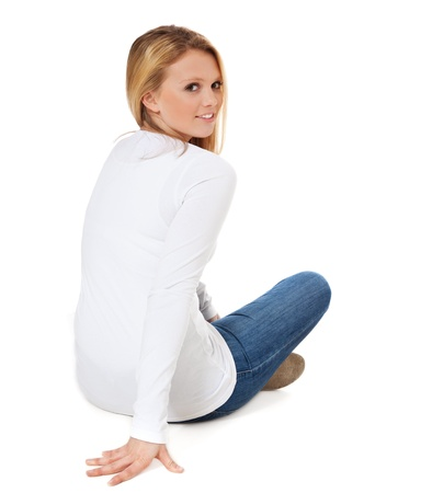 Back view of an attractive teenage girl sitting on the floor  All on white background