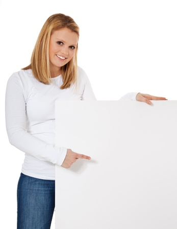 Attractive teenage girl standing next to blank white sign  All on white background   Stock Photo - 12859984
