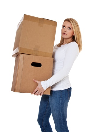 Attractive teenage girl carrying moving boxes  All on white background  photo