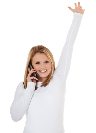 scandinavian descent: Attractive teenage girl getting good news during phone call  All on white background   Stock Photo