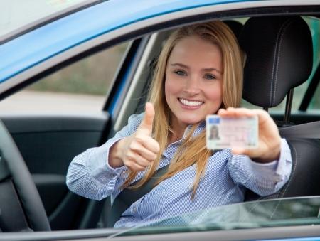 conducci�n: Mujer joven atractiva muestra su carn� de conducir Foto de archivo