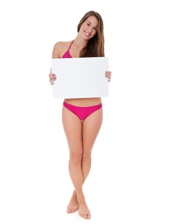 Attractive teenage girl in bikini holding blank white sign  All on white background