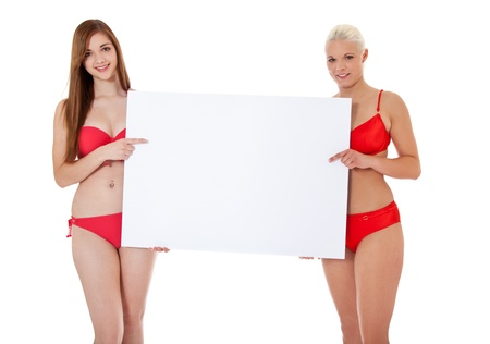 Two attractive girls in bikini holding blank white sign  All on white background   photo