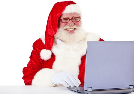 Santa Claus in authentic look using laptop  All on white background   photo
