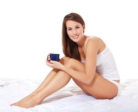 wit ondergoed: Aantrekkelijke jonge vrouw in wit ondergoed met een kopje koffie Alle op een witte achtergrond