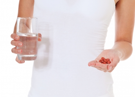 Female person holding glass of water and pile of pharmaceuticals  All on white background   photo