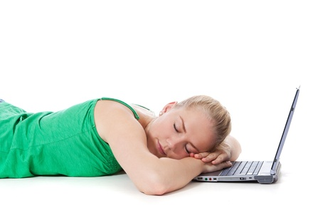 scandinavian descent: Attractive teenage girl sleeping next to her laptop  All on white background   Stock Photo